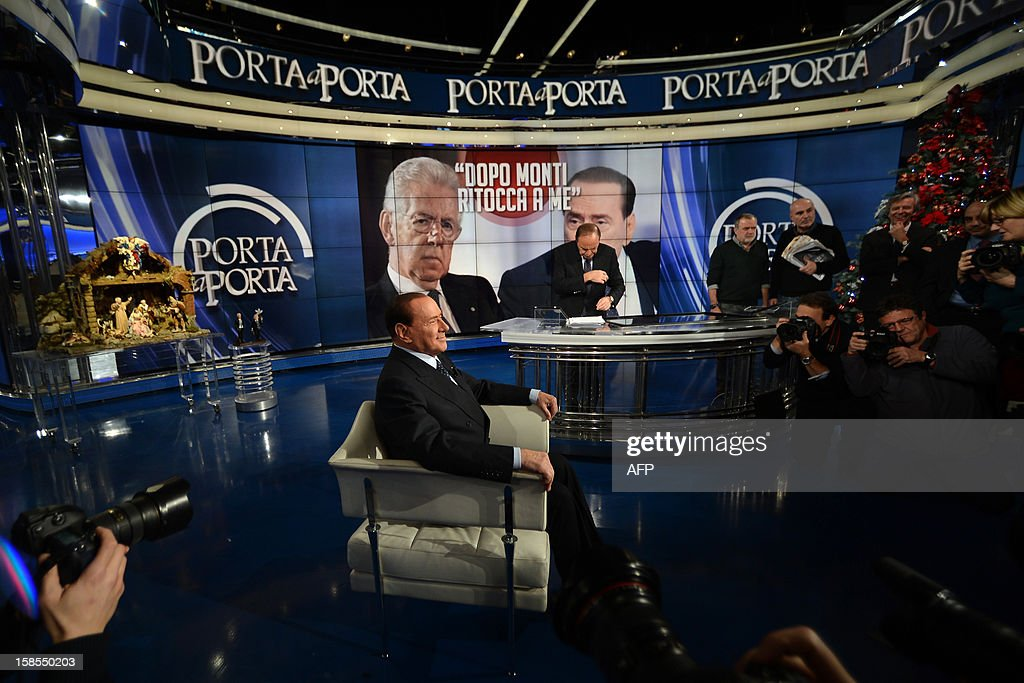 Former Italian Prime Minister Silvio Berlusconi takes place on the set of RAI 1 television programme 'Porta a Porta' on December 18, 2012 in Rome. Silvio Berlusconi the day before said a German-dominated Europe had imposed austerity on Italy as the three-time prime minister prepares for his sixth election campaign in two decades in politics. Flower reads 'No come back'. AFP PHOTO / FILIPPO MONTEFORTE