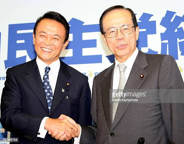 Former Japanese Foreign Minister and Secretary General of the Liberal Democratic Party Taro Aso shakes hand with former Chief Cabinet Secretary Yasuo...
