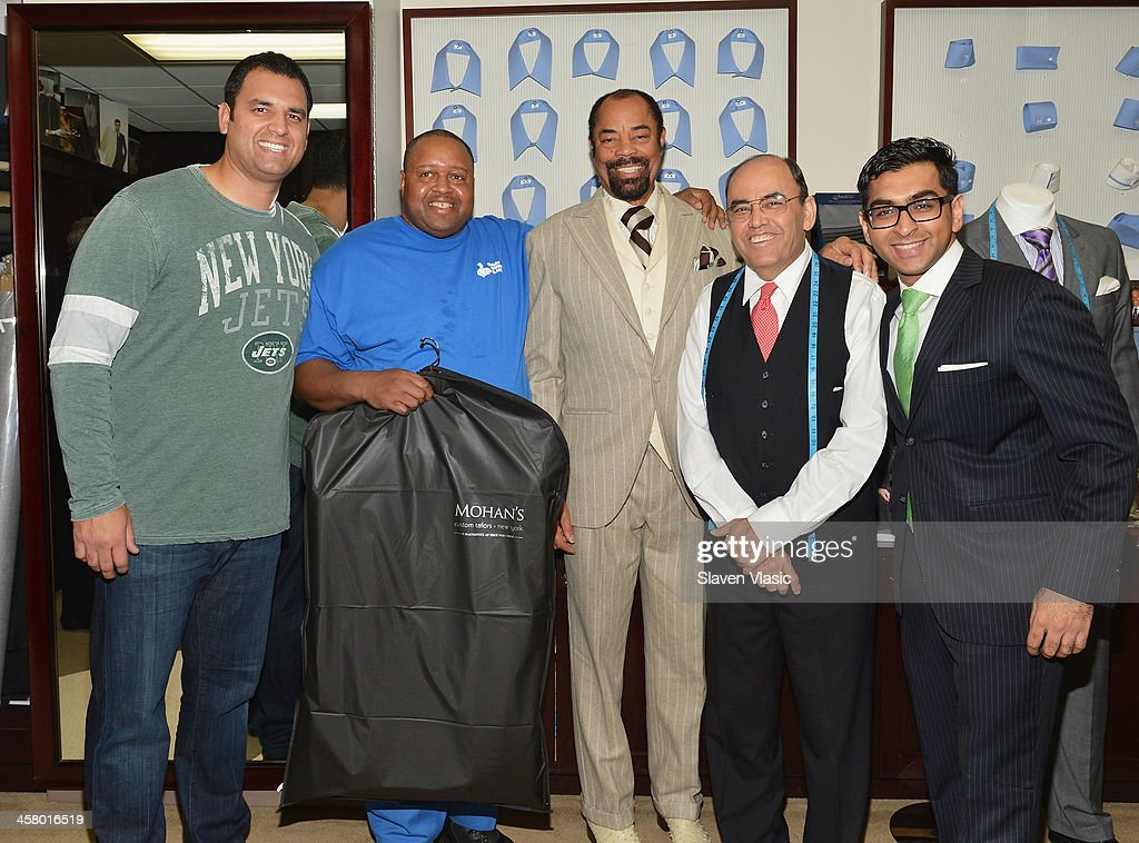Former Jets player Anthony Becht, Doe Fund program member/recipient of a suit, former basketball player Walt 'Clyde' Frasier, Mohan Ramchandani and guest attend the 2013 Mohan's Winter Coat Drive benefiting The Doe Fund at Mohan's Custum Tailors on December 19, 2013 in New York, United States.