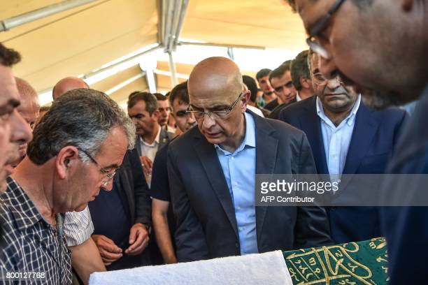 Former journalist turned CHP lawmaker Enis Berberoglu carries his stepfather's coffin during the funeral ceremony on June 23 2017 in Istanbul...