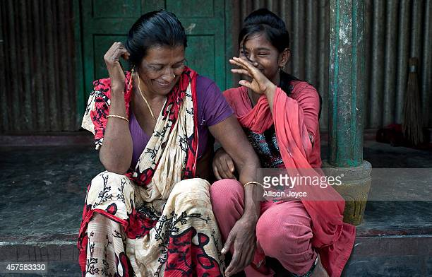 Former Kandapara brothel sex worker 50 year old Rekha sits with 13 year old Asthma Reyamoni on October 18 2014 in Tangail Bangladesh Rakha ran away...