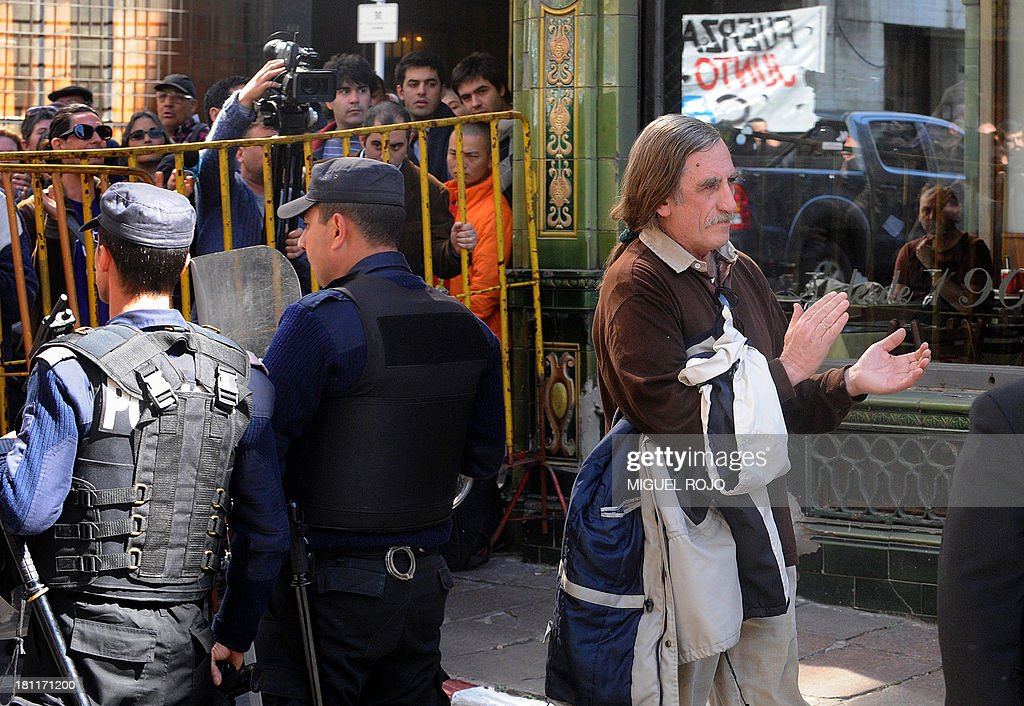Former leader of the leftist MLN-Tupamaros guerrilla movement, Jorge Zabalza (R), who was imprisoned for 13 years during Uruguay's dictatorship, heads to the court to testify for his participation in a case involving protests at the Supreme Court of Justice when judge Mariana Mota was to take office after being transferred from a criminal court to a civil one, in Montevideo, on September 19, 2013. Zabalza was among a group of human rights activists who in February this year occupied the Supreme Court in support of Mota, after she was transferred from a criminal court where she worked on about 50 cases of human rights abuses during the 1973-1985 dictatorship in Uruguay, to a civil court. AFP PHOTO / Miguel ROJO