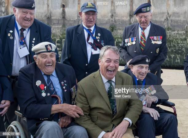 Former leader of UKIP Nigel Farage poses for a photograph as he joins veterans on the beach at Arromanches as they take part in commemorations to...