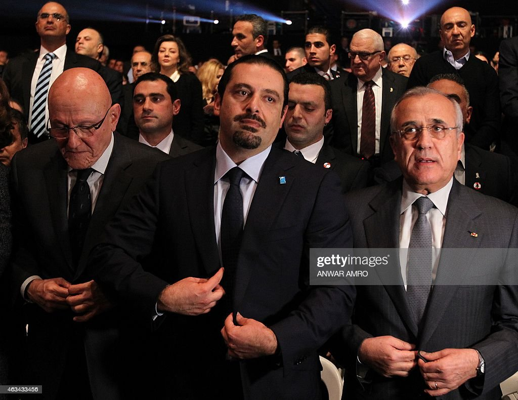 Former Lebanese prime minister Saad Hariri (C), flanked by Lebanese Prime Minister Tammam Salam (L) and former Lebanese president Michel Sleiman, attends a gathering to mark the tenth anniversary of the assassination of his father and former prime minister Rafiq Hariri, on February 14, 2015, at the Biel Convention Centre in downtown Beirut. Lebanese paid their respects to the late former prime minister, a decade after his assassination in a massive and shocking suicide bombing that destabilised the fragile country.