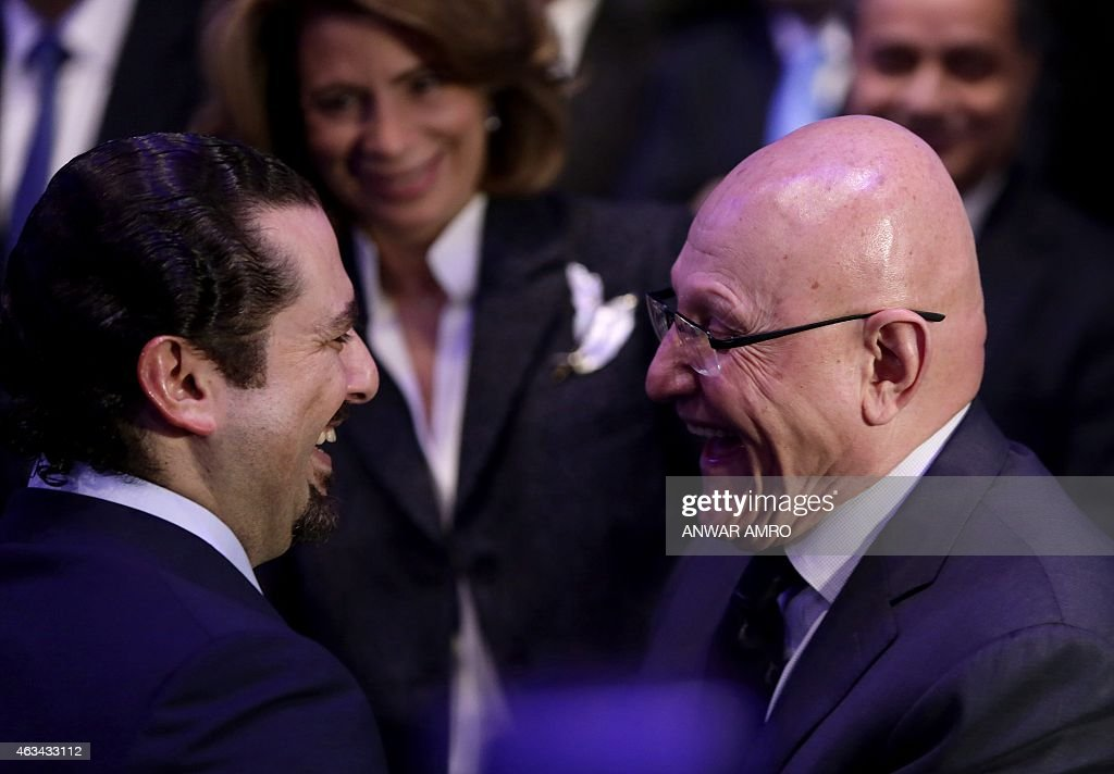 Former Lebanese prime minister Saad Hariri (L) shares a laugh with Lebanese Prime Minister Tammam Salam as he attends a gathering to mark the tenth anniversary of the assassination of his father and former prime minister Rafiq Hariri, on February 14, 2015, at the Biel Convention Centre in downtown Beirut. Lebanese paid their respects to the late former prime minister, a decade after his assassination in a massive and shocking suicide bombing that destabilised the fragile country.