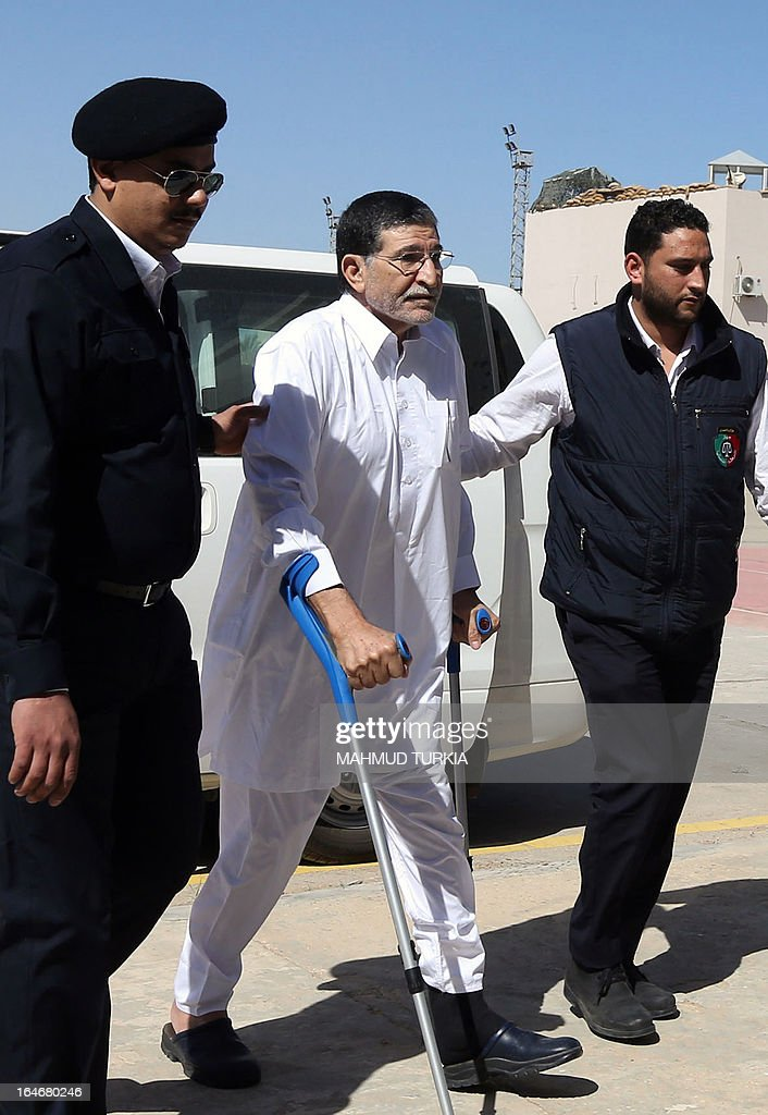 Former Libyan foreign intelligence chief Bouzid Dorda (C) is escorted by police as he arrives for a hearing in his trial at a court in Tripoli on March 26, 2013. The former foreign intelligence chief, the first of Moamer Kadhafi's top officials to face justice, is accused of ordering security forces to use live ammunition against demonstrators last year.