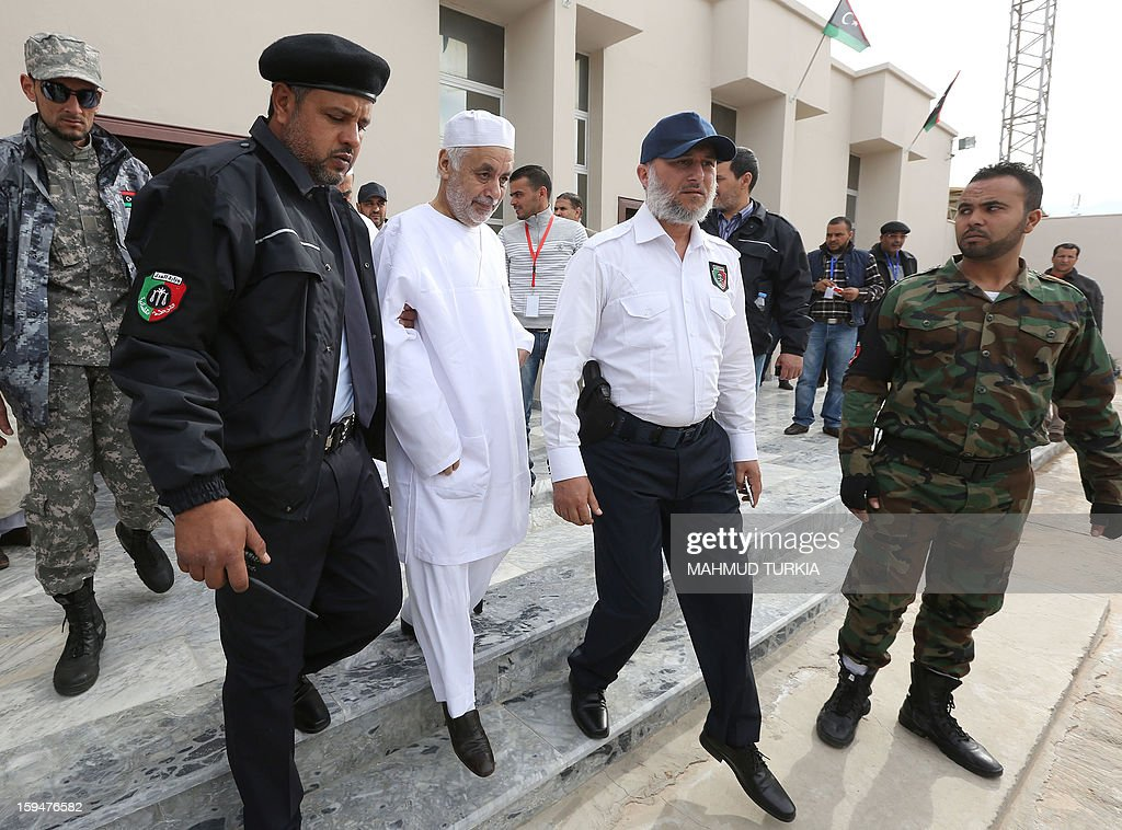 Former Libyan prime minister Baghdadi al-Mahmudi (C) is escorted by police to his trial, on January 14, 2013, in Tripoli. The trial of Mahmudi, late Libyan dictator Moamer Kadhafi's last prime minister, continues in the Libyan capital as he faces charges of 'prejudicial acts against the security of state'.