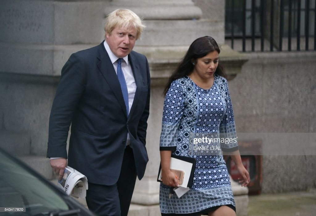 Former London mayor and Brexit campaigner Boris Johnson (L) walks across a carpark by the Houses of Parliament and Portcullis House in central London on June 28, 2016. Popular British MP Boris Johnson is one step away from his dream of becoming Prime Minister, but the shadow of the ill-tempered EU referendum campaign looms large over his leadership bid. / AFP / DANIEL
