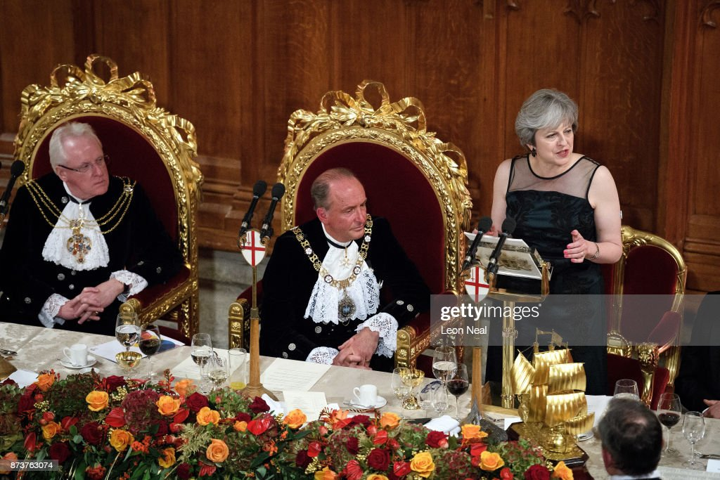 Former Lord Mayor of London Andrew Parmley (L) and Lord Mayor of London Charles Bowman (C) listen as Britain's Prime Minister Theresa May delivers her speech at the annual Lord Mayor's banquet on November 13, 2017 in London, England. The Prime Minister spoke of various global issues, including Russia's involvement in destablising countries and elections around the world.