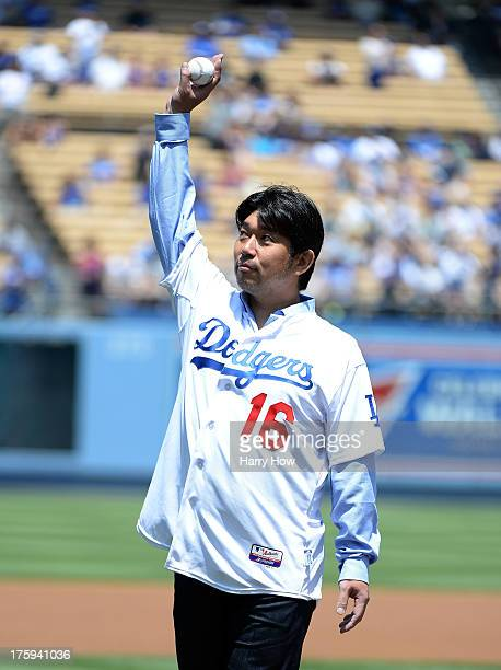 Former Los Angeles Dodgers Hideo Nomo of Japan waves to the crowd before his ceremonial first pitch before the game against the Tampa Bay Rays at...