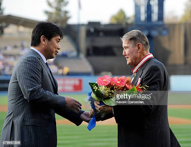 Former Los Angeles Dodgers pitcher Hideo Nomo presents flowers to former Dodgers President Peter O'Malley after he received The Order of the Rising...