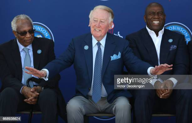 Former Los Angeles Dodgers play by play announcer Vin Scully gestures onstage as former MLB player Frank Robinson left and Los Angeles Dodgers owner...