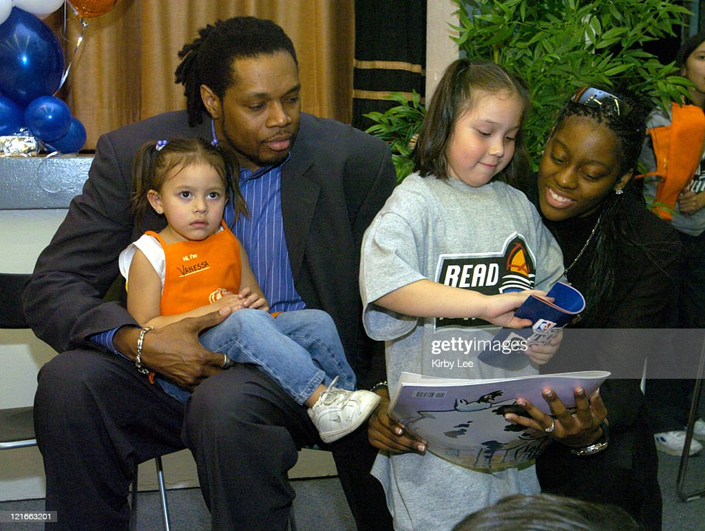 Former Los Angeles Laker Sam Perkins and Nikki Teasley of the Los Angeles Sparks read books to children during unveiling ceremony of reading and...