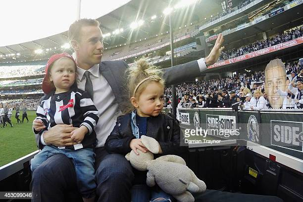 Former Magpies captain Nick Maxwell who recently retired does a lap on honour with his children before the round 19 AFL match between the Collingwood...