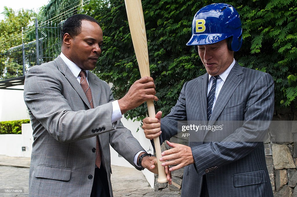US former Major League Baseball player and now Brazlian National Baseball team coach Barry Larkin (L), teaches Japanese consul general Noriteru Fukushima how to grab the bat during a reception at the Japanese consulate for their first participation in the World Baseball Classic (WBC), in Sao Paulo, Brazil, on Februrary 5, 2013. WBC first round will start from March 2 in Japan, Taiwan, Puerto Rico and the US with 16 teams from around the world taking part. AFP PHOTO/Yasuyoshi CHIBA