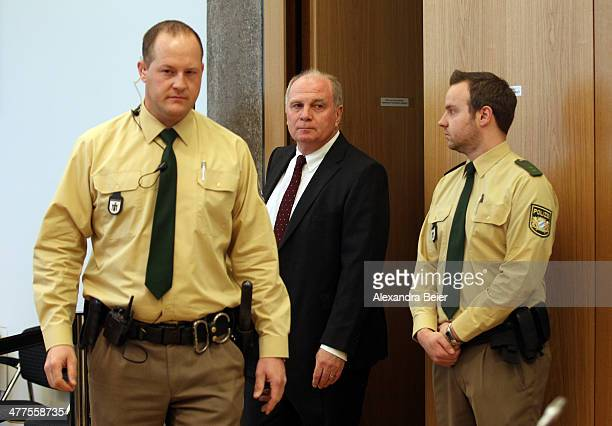 Former manager of Bayern Muenchen Uli Hoeness arrives for his trial escorted by police men at the justice palace court room on March 10 2014 in...