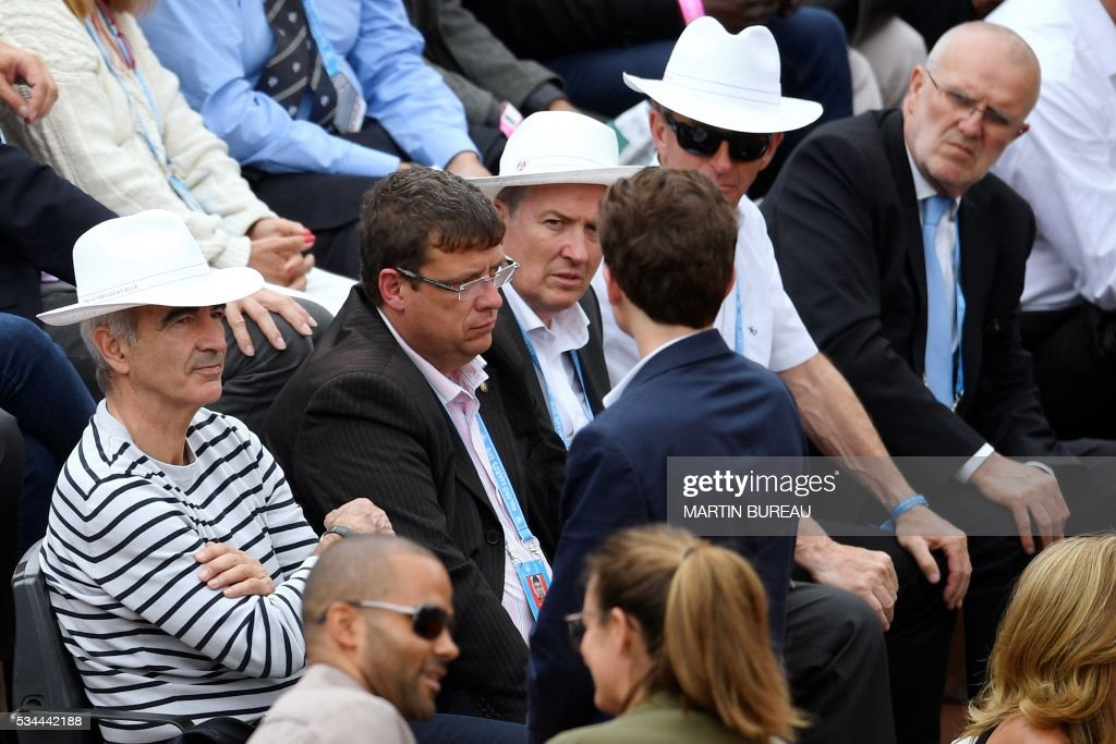 Former manager of the French national football team Raymond Domenech (L) attends the men's second round match between France's Jo-Wilfried Tsonga and Cyprus' Marcos Baghdatis at the Roland Garros 2016 French Tennis Open in Paris on May 26, 2016. / AFP / MARTIN