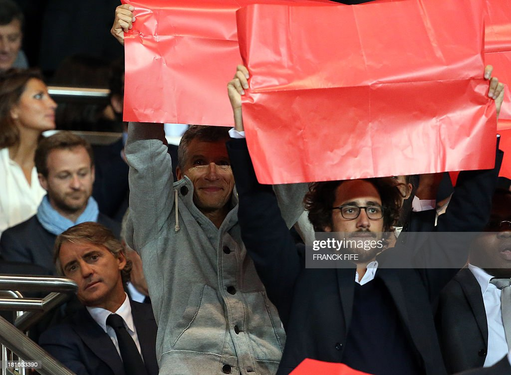 Former Manchester City's Italian manager Roberto Mancini, French TV host Nagui and French President's son Thomas Hollande react before the French L1 football match Paris Saint-Germain (PSG) vs Monaco (ASM), on September 22, 2013 at the Parc des Princes stadium in Paris.