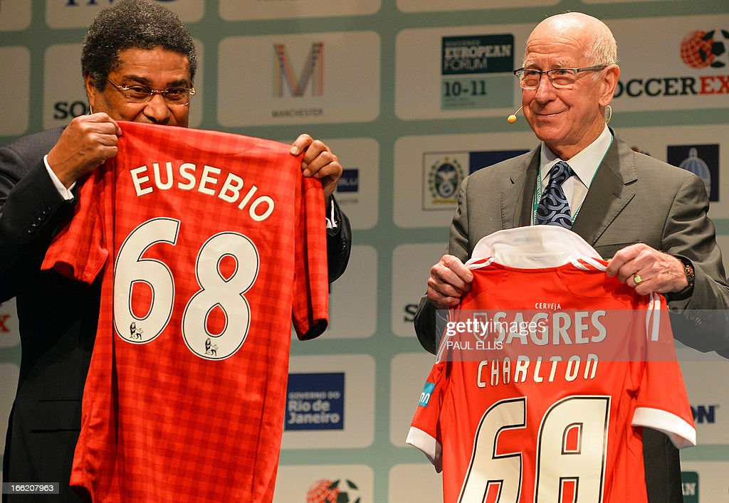 Former Manchester United and England footballer Sir Bobby Charlton (R) exchanges shirts with former Benfica and Portugal player Eusebio during the Soccerex European Forum in Manchester, north-west England, on April 10, 2013. Soccerex is a football business event, conference and exhibition.