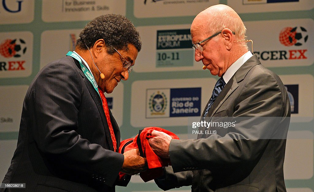 Former Manchester United and England footballer Sir Bobby Charlton (R) exchanges shirts with former Benfica and Portugal player Eusebio during the Soccerex European Forum in Manchester, north-west England, on April 10, 2013. Soccerex is a football business event, conference and exhibition. AFP PHOTO/PAUL ELLIS