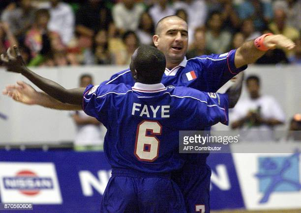 Former Manchester United football player Eric Cantona celebrates with Mamadou Faye after a score during beach soccer in Bangkok 12 May 2001 France...