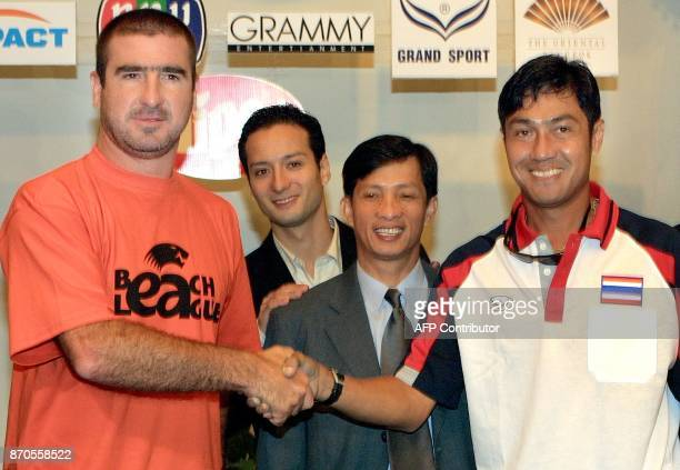 Former Manchester United football player Eric Cantona shakes hands with former Thai star football player Piyapong Pieuon during a press conferrence...