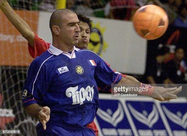 Former Manchester United football player Eric Cantona vies for the ball with Thai soccer player Pataya Piamkhum during beach soccer in Bangkok 12 May...