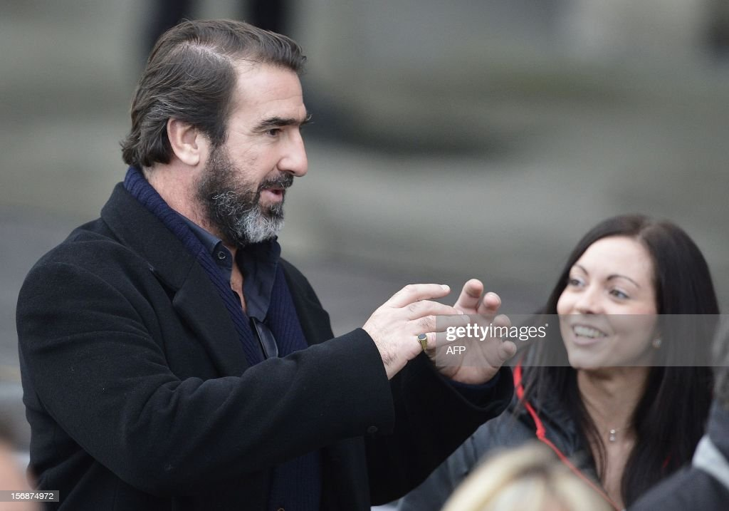 Former Manchester United player Eric Cantona (L) reacts during the unveiling of a statue of Manchester United's manager Alex Ferguson at Old Trafford stadium in Manchester, northern England on November 23, 2012. Manchester United manager Alex Ferguson quipped that he was 'out-living death' after a bronze statue of him was unveiled outside Old Trafford. The nine-foot statue was commissioned in November last year to mark Ferguson's 25th anniversary at the club, when the North Stand was renamed in his honour. AFP PHOTO/POOL/ Nigel Roddis