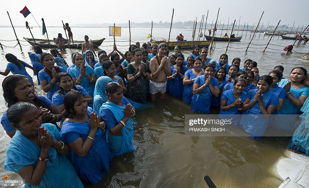 Former manual scavengers, along with founder chairman of Sulabh Internationa,l Bindeshwari Pathak (C), offer prayer at Sangam, the confluence of the Ganges, Yamuna and mythical Saraswati rivers during the Kumbh Mela in Allahabad on February 7, 2013. 100-odd former scavenger women from Rajasthan's Alwar and Tonk districts, rehablitated by NGO Sulabh International, took a holy dip at Sangam, performed puja and had lunch with priests at the Kumbh Mela. AFP PHOTO/ Prakash SINGH