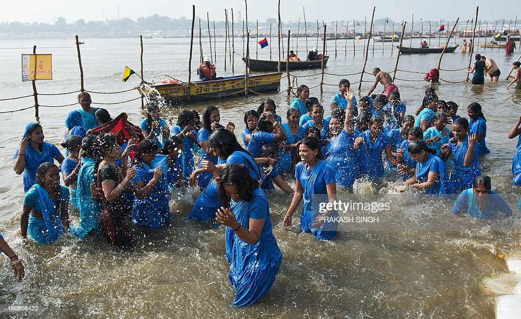 Former manual scavengers take a 'holy dip' at Sangam, the confluence of the Ganges, Yamuna and mythical Saraswati rivers during the Kumbh Mela in Allahabad on February 7, 2013. 100-odd former scavenger women from Rajasthan's Alwar and Tonk districts, rehablitated by NGO Sulabh International, took a holy dip at Sangam, performed puja and had lunch with priests at the Kumbh Mela. AFP PHOTO/ Prakash SINGH