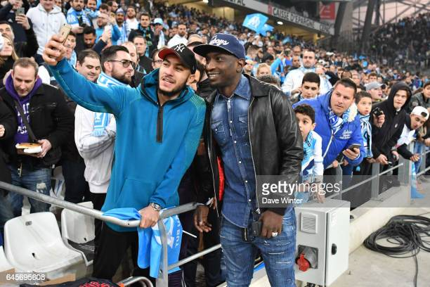 Former Marseille player Mamadou Niang poses for a selfie with fans before the French Ligue 1 match Marseille and Paris Saint Germain at Stade...