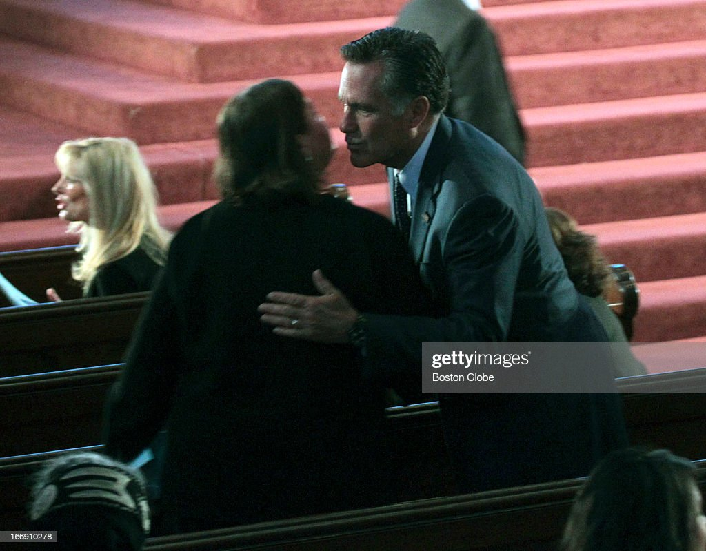 Former Massachusetts Governors Jane Swift and Mitt Romney kiss before the special interfaith service led by President Barack Obama in memory of the victims of the bombing at the 117th Boston Marathon.