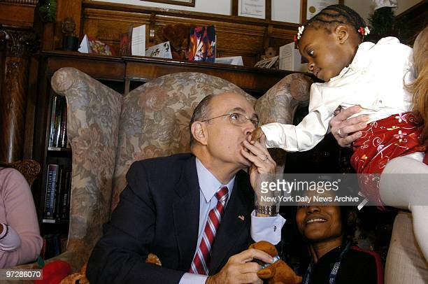 Former Mayor Rudy Giuliani kisses the hand of a little girl as he visits Hale House in Harlem on the day before Christmas to pass out gifts and read...