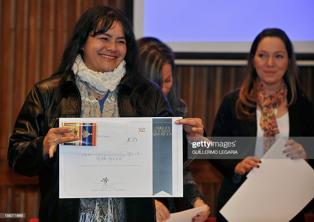 A former member of an illegal armed group shows her diploma after receiving it from the Colombian Agency for Reintegration (ACR) during a ceremony in Bogota, on December 11, 2012. The ACR certified on Tuesday a group of 59 people - former members of the illegal armed groups Revolutionary Armed Forces of Colombia (FARC) and United Self-Defense Forces of Colombia (AUC) - who completed their reintegration to society. AFP PHOTO/Guillermo Legaria