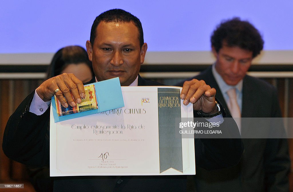 A former member of an illegal armed group shows his diploma after receiving it from the Colombian Agency for Reintegration (ACR) during a ceremony in Bogota, on December 11, 2012. The ACR certified on Tuesday a group of 59 people - former members of the illegal armed groups Revolutionary Armed Forces of Colombia (FARC) and United Self-Defense Forces of Colombia (AUC) - who completed their reintegration to society. AFP PHOTO/Guillermo Legaria