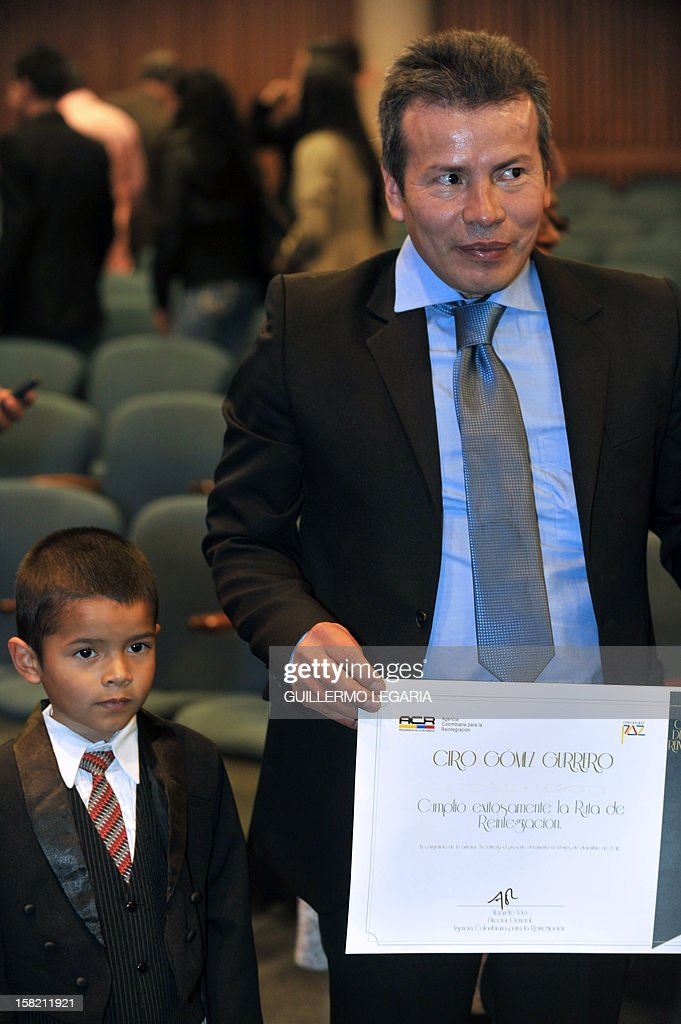 A former member of an illegal armed group stands next to his son after receiving his diploma from the Colombian Agency for Reintegration (ACR) during a ceremony in Bogota, on December 11, 2012. The ACR certified on Tuesday a group of 59 people - former members of the illegal armed groups Revolutionary Armed Forces of Colombia (FARC) and United Self-Defense Forces of Colombia (AUC) - who completed their reintegration to society. AFP PHOTO/Guillermo Legaria
