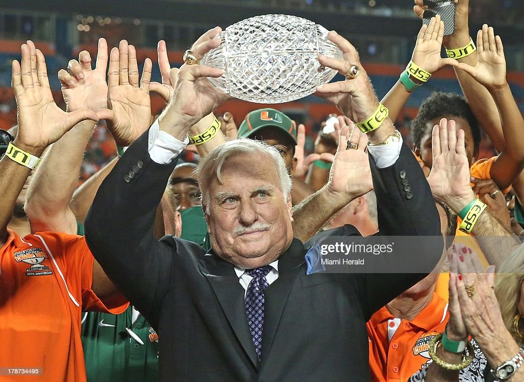 Former Miami coach Howard Schnellenberger raises the 1983 NCAA National Championship trophy during a halftime ceremony during action against Florida Atlantic at Sun Life Stadium in Miami Gardens, Florida, on Friday, August 30, 2013.