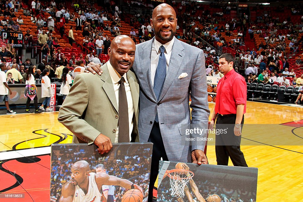 Former Miami Heat players Tim Hardaway, left, and Alonzo Mourning receive prints of themselves after giving an interview at halftime of a game between the Portland Trail Blazers and Heat on February 12, 2013 at American Airlines Arena in Miami, Florida.