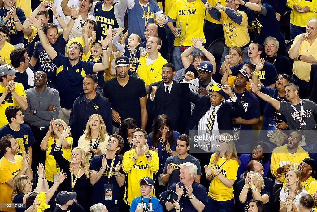Former Michigan Wolverines players Juwan Howard, Jimmy King, Ray Jackson and Jalen Rose cheer on the Wolverines as they take on the Louisville Cardinals during the 2013 NCAA Men's Final Four Championship at the Georgia Dome on April 8, 2013 in Atlanta, Georgia.
