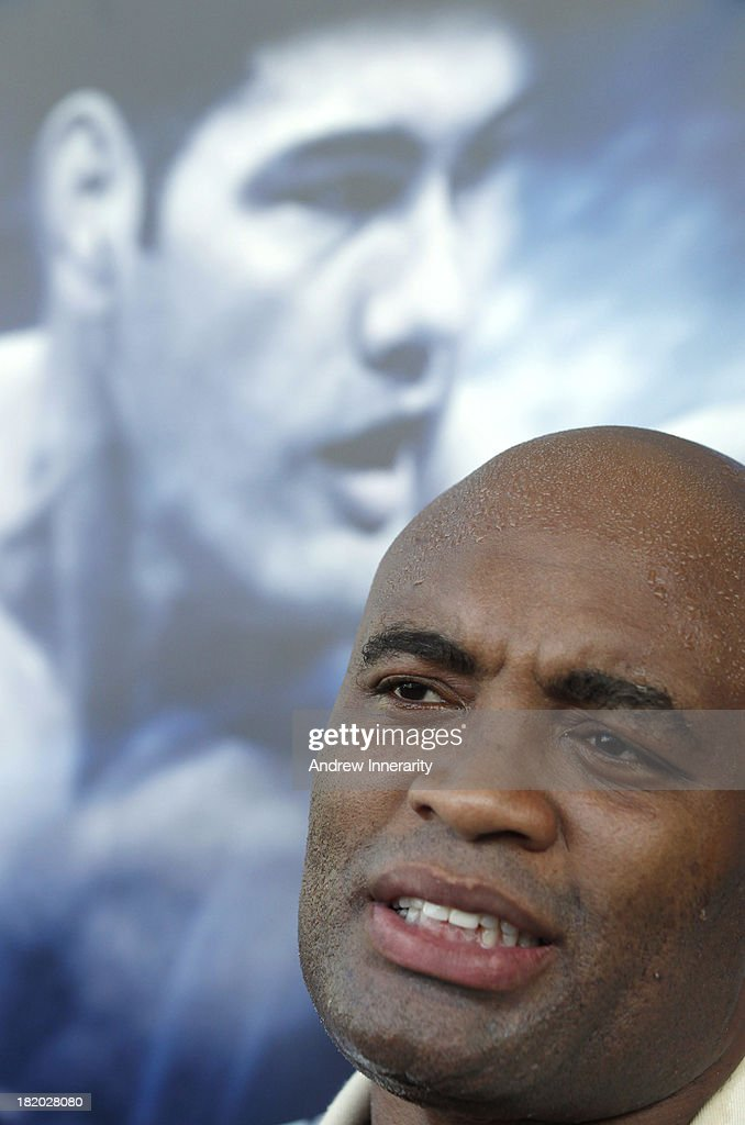 Former middleweight champion Anderson Silva speaks to the media in front of this poster of his opponent, UFC middleweight champion Chris Weidman during the UFC 168: Weidman v SIlva 2 press tour at Klipsch Amphitheater at Bayfront Park on September 27, 2013 in Miami, Florida.