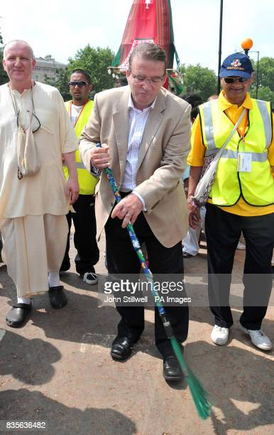 Former Minister for London Tony McNulty sweeps a clean path in front of three giant decorative wheeled shrines which were hand pulled from Hyde Park...