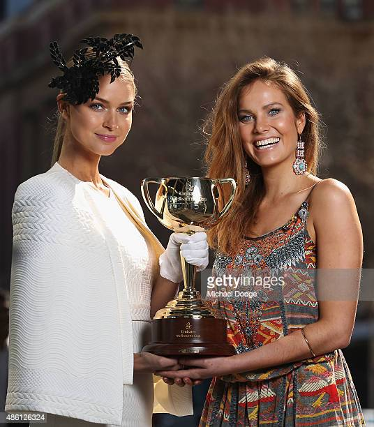 Former Miss Universe Australia Renae Ayris and model Kirsten Clemens pose with the Melbourne Cup during the Melbourne Cup Carnival launch at Southern...