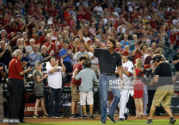 Former MLB pitcher Randy Johnson waves to fans as he takes the field for the ceremonial first pitch before the Opening Day MLB game between the...