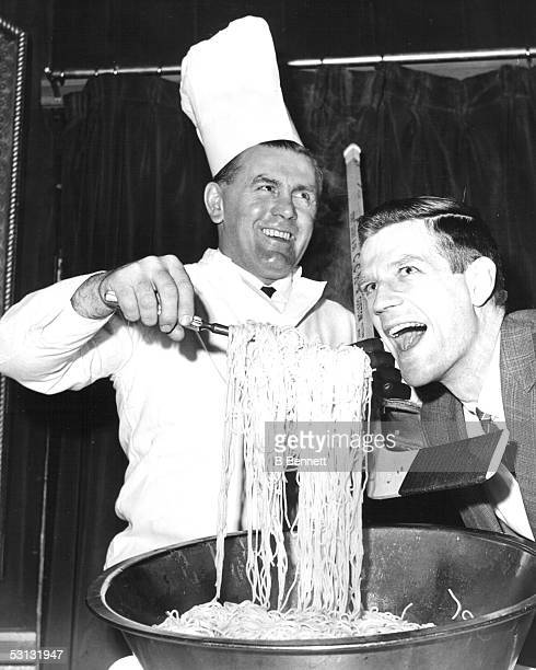 Former Montreal Canadien Maurice Richard feeds spaghetti to former teammate Phil Goyette of the New York Rangers at a hockey writer's luncheon on...