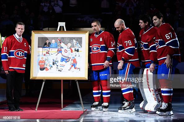 Former Montreal Canadien player Saku Koivu poses for a photo with family former teammates during a ceremony honouring the former team captain prior...