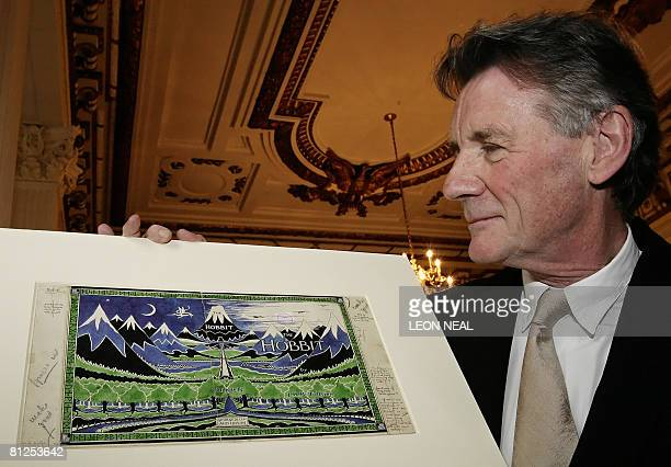 Former Monty Python actor and Oxford University graduate Michael Palin holds an original artwork of JRR Tolkien's 'The Hobbit' as he attends the...