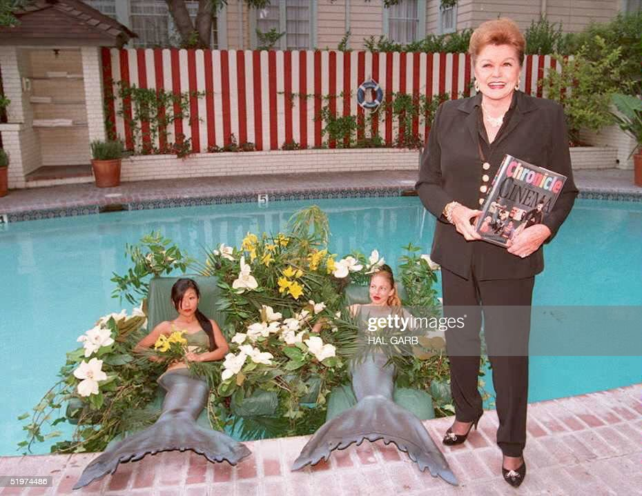 Former movie star <a gi-track='captionPersonalityLinkClicked' href=/galleries/search?phrase=Esther+Williams&family=editorial&specificpeople=123838 ng-click='$event.stopPropagation()'>Esther Williams</a> poses for photographers poolside at the Chateau Marmont Hotel 11 May with two woman dressed as mermaids. Williams hosted the party to help launch a new coffee-table book, 'Chronicle of the Cinema, 100 Years of the Movies.' The mermaids are Julie Yoneyama(L) and Lisa McDonald(R).