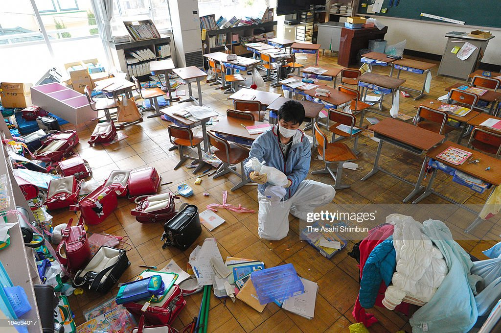Former Namie Elementary School teacherTakakatsu Watanabe cleans former his classroom that remains untouched after the Fukushima Daiichi Nuclear Power Plant meltdown, on March 23, 2013 in Namie, Fukushima, Japan. Japanese government will reclassify the radiation contaminated town by the radioactive level from April 1.