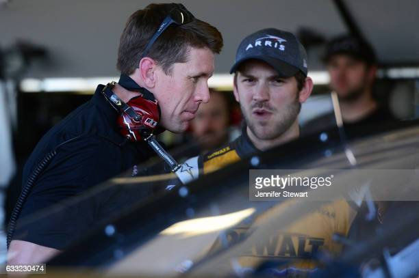 Former NASCAR Cup driver Carl Edwards looks over the car alongside Monster Energy NASCAR Cup Series driver Daniel Suarez during a NASCAR testing at...