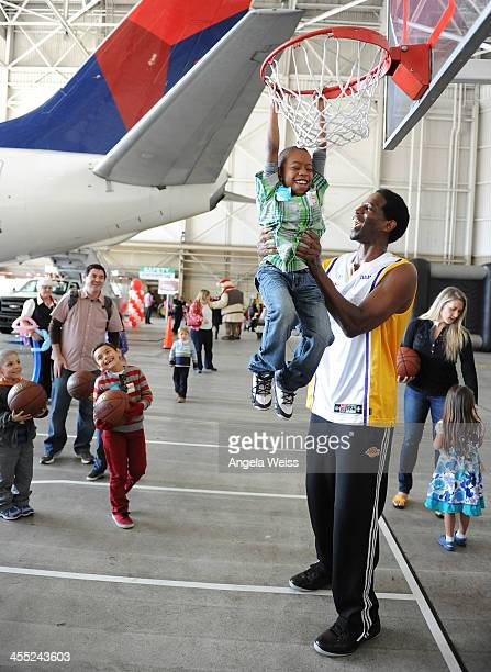 Former NBA basketball player AC Green attends Delta Air Lines' celebration of Holiday in the Hangar 'Flight to the North Pole' for children of...